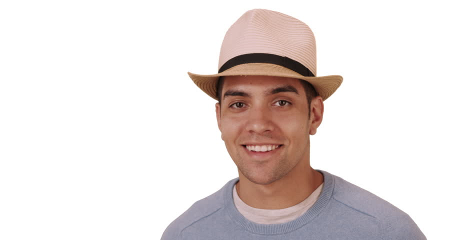 Happy millennial Hispanic mixed race man standing on white background with hat. Fashionable young Mexican man in 20s wearing fedora. Copy space. 4k