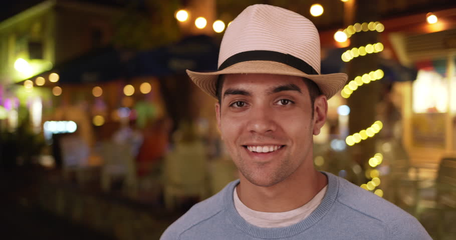 Happy millennial Latino mixed race man on vacation at night. Fashionable young Mexican man in 20s wearing fedora with lights in background. 4k