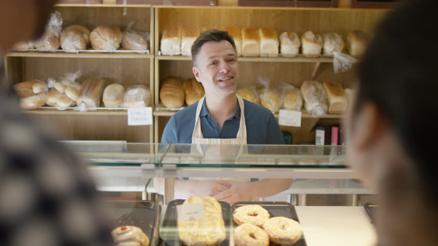 4K Couple in a bakery shop making contactless payment by cell phone (UK-Oct 2016)