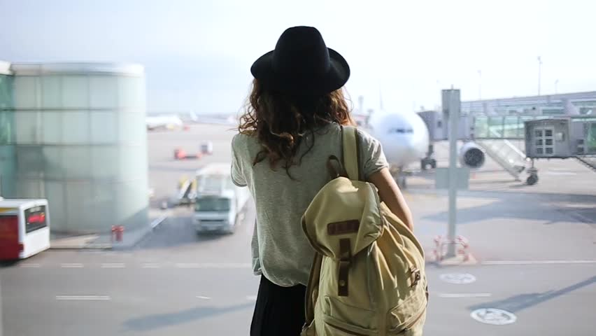 girl standing at the window in airport terminal.
