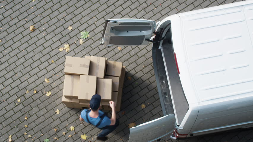 Delivery Man Loads his Commercial Van with Cardboard Boxes. Shot on RED Cinema Camera in 4K (UHD)