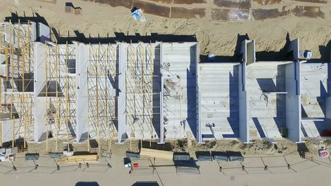 FULLHD Aerial View of a construction site with houses and walls on the ground floor showing working man. Sunny weather. Drone shot, 90 degrees angle, ascending movement.