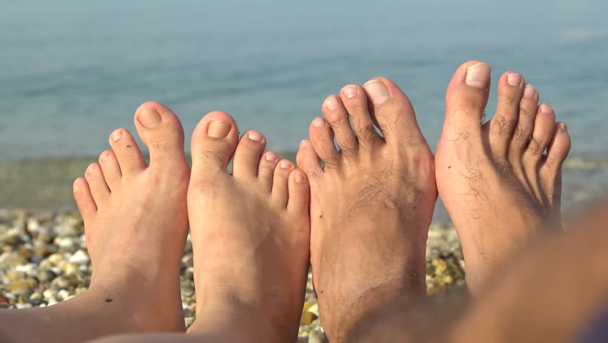 Two pairs of Caucasian feet, male and female, on a sea beach. Couple on a summer vacation. Couple on a beach. | Shutterstock HD Video #21561706