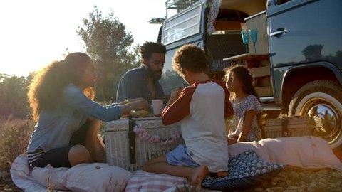 Family eating picnic outside their camper van at sundown