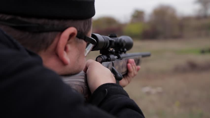 Man in hunting equipment hold hunting rifle with a telescopic sight and shoot the target on firing range, close-up.