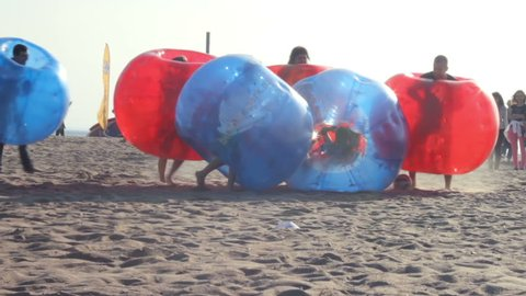 Zorbing on the sand. Open air Active games inside Zorb bubble Balls. Team of Teenagers Playing trendy Zorb Football on the Beach. Tercentenary park of Saint-Petersburg, Russia, june 2016
