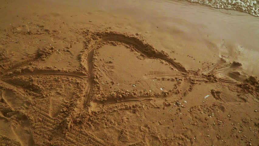 Heart draw on sand. Heart shape on sand background. Close up of heart on sand. Heart symbol on golden sand with sea waves