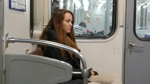 Tired woman sit alone at running subway train, shake during motion. Faint smile on sad face, one passenger at old style carriage, Saint Petersburg metro. Next wagon seen through window glass