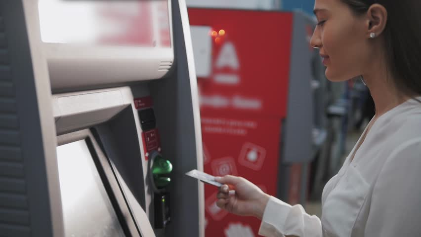 young woman inserting a credit card to ATM, beautiful girl banking