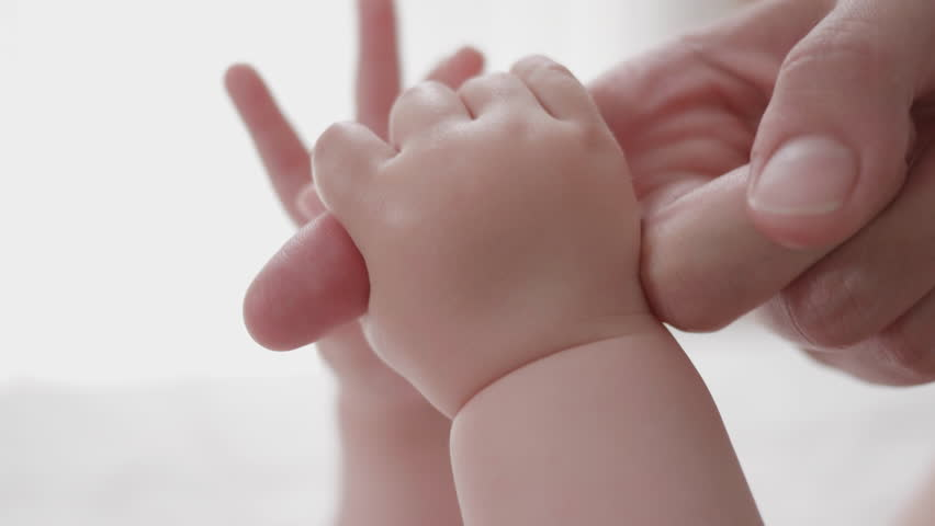 Close-up shot of baby's little cute hand reaching for mother's loving hand. While holding her finger she caresses his hand.