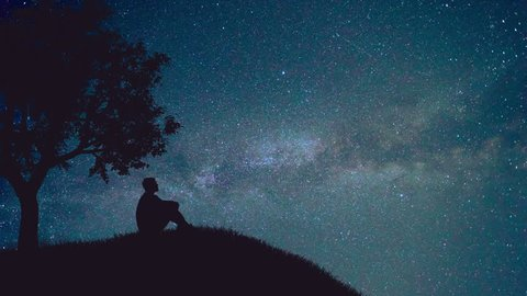 The man sit near the tree on the background of starry sky. Time lapse