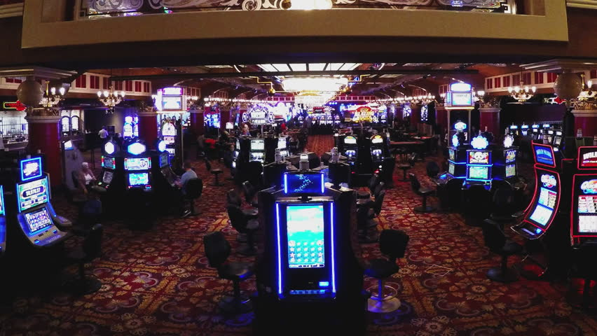 LAUGHLIN, NV/USA: November 21, 2016- Wide shot of a slot machine gaming area in a gambling casino. Empty slot machines stand at attention with inviting lights awaiting patron's money.