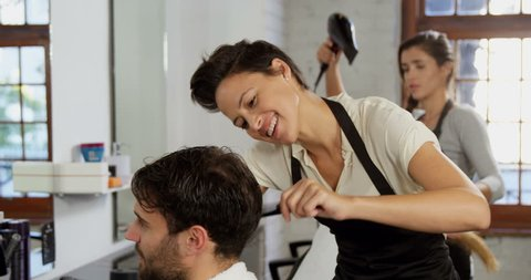 Side view of Caucasian hairdresser trimming her client hair in the hair salon
