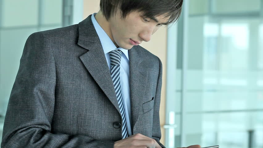 Close-up of a serious Asian businessman using a tablet