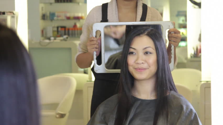 MEDIUM SHOT, Hairdresser showing to customer hair cut