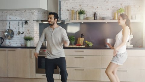Happy Couple Creatively Dances in the Kitchen. Both are Adorable and Smiling. Shot on RED Cinema Camera in 4K (UHD).