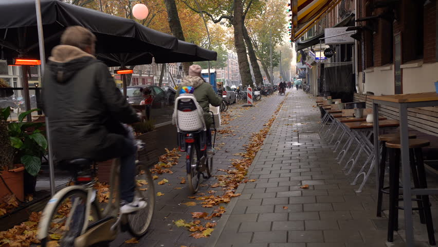 Street in the central area of Amsterdam. Early morning. Peoples drive to work. Busy peoples ride on bicycles
