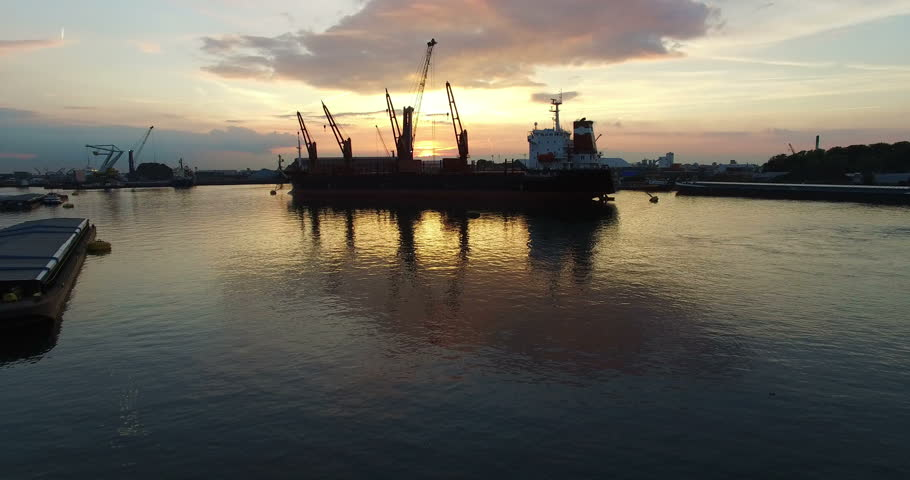 Anchored Cargo ship in a harbor unloading cargo with a large moving crane with a beautiful orange sunset in the background (cargo transhipment). Aerial Ultra HD view forward movement while ascending.
