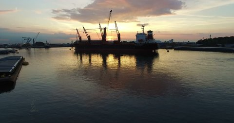 Anchored Cargo ship in a harbor unloading cargo with a large moving crane with a beautiful sunset in the background (cargo transhipment). Aerial Drone Ultra HD view forward movement while ascending.