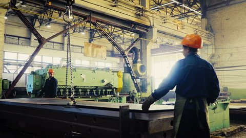 two workers of the plant or factory lift sheet metal. Cling and crane hooks are on the machine for cutting metal blade