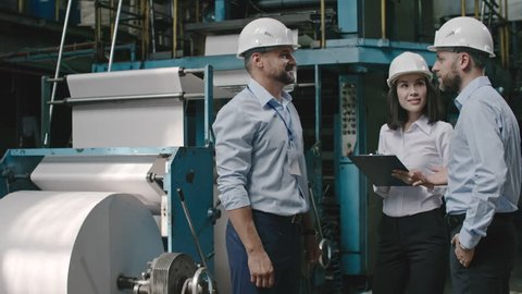 Male engineers in formalwear and hard hats standing before industrial paper machinery making deal and shaking hands as their female colleague making notes in clipboard
