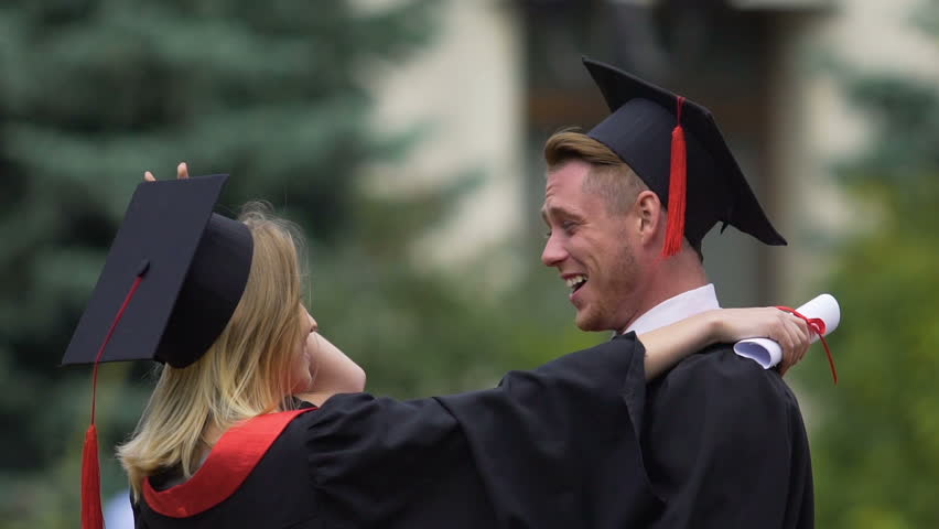 Young man and woman in love graduating from university, kissing and hugging | Shutterstock HD Video #21796486
