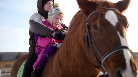 Hippotherapy for kid with cerebral palsy syndrome at winter cold day - contact kids therapy and rehabilitation horse-riding club - young girl and her parents on horse, close up