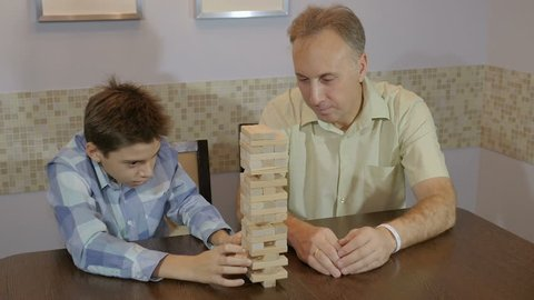 schoolboy makes high tower with matchboxes on brown table expresses joy and father watches sitting nearby in room