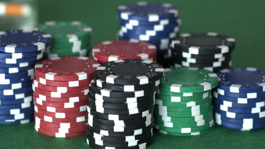Player puts back on table glass with drink and reaches out to grab poker chips, concept of victory, playing card games, gamble. Close up, shallow DOF, 4K Ultra HD.