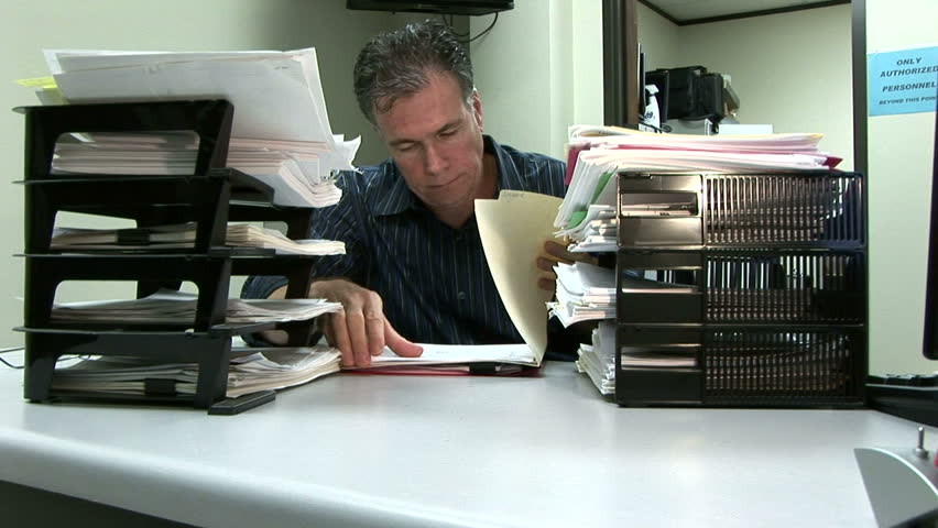 A man at his desk showing signs of being overworked