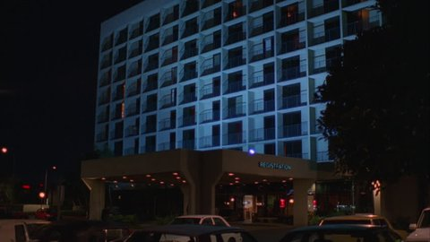 """night Raked right 7 story modern ND white hotel, middle class with balconies an overhang with """"Registration"""" (May 1995)"""