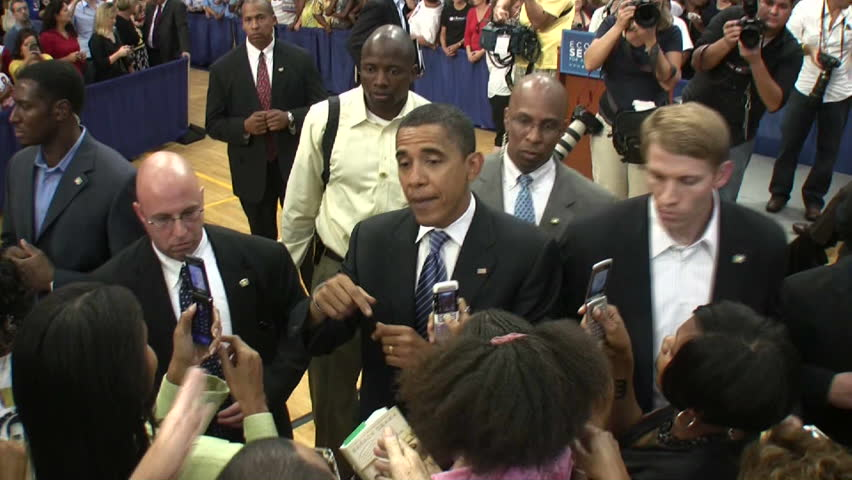 Barack Obama shakes hands surrounded by the secret service.