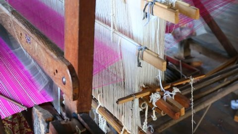 The local worker is weaving with handloom in the factory, inle lake, myanmar