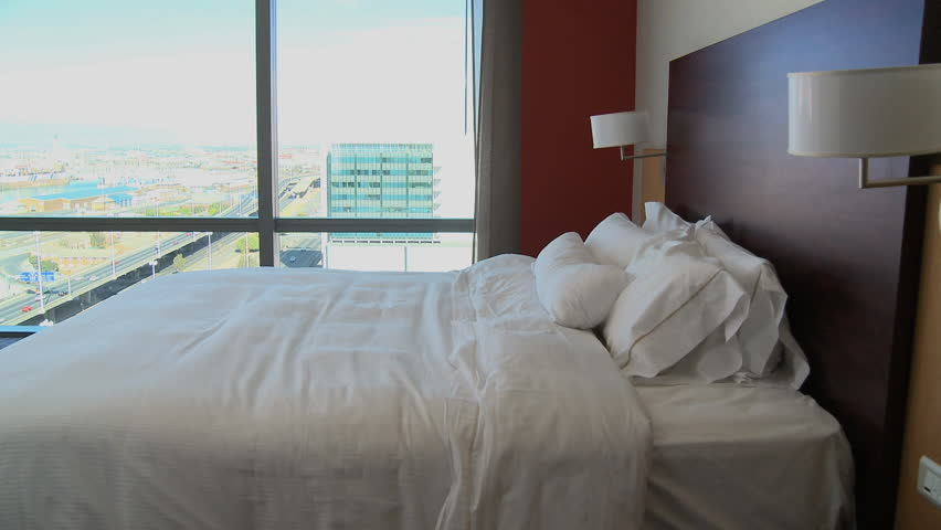 LONG SHOT PAN OF A BUSINESSWOMAN WALKING INTO HER HOTEL ROOM AND LYING ON THE BED