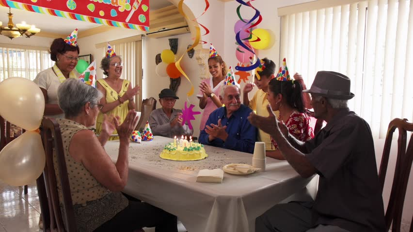 Group of old friends and family celebrating senior man birthday in retirement home. Happy elderly people having fun during party. Grandfather blowing candles on cake and smiling. Slow motion