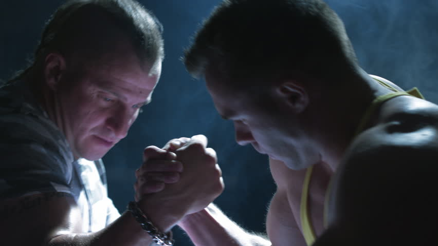 A couple of muscular man measuring forces. Arm-wrestling in the gym