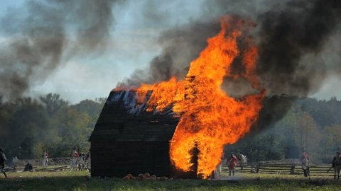 VIRGINIA - OCTOBER 2015 - Reenactment, large-scale, epic American Revolutionary War anniversary recreation -- in the middle of battle.  House and Farm burned by British Soldiers in revenge. Attack