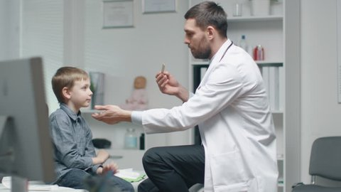Male Doctor Checks Young Boys Throat. Nurse is Busy in the Background.