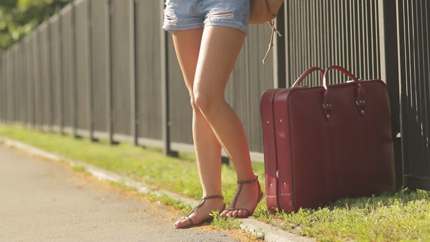 girl traveler with suitcase aside of road