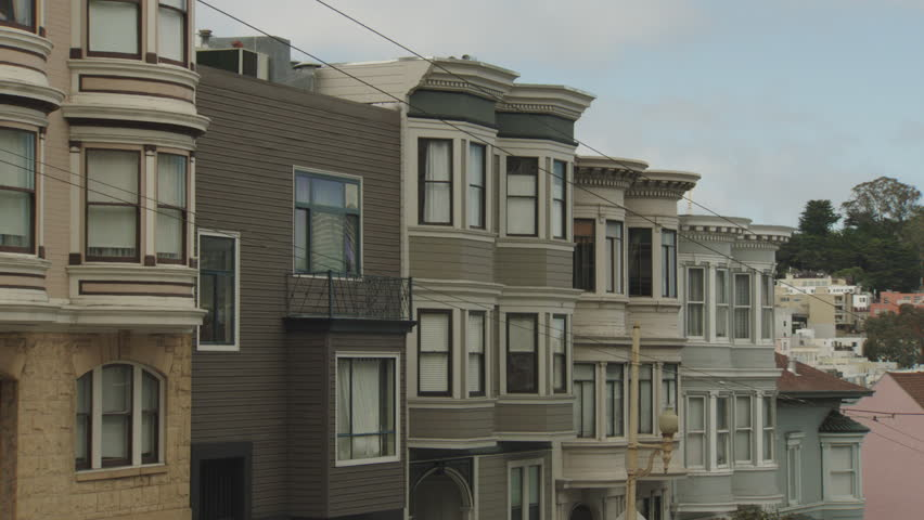 Day row Victorian style apartments then pan right hold Coit Tower residential neighborhood area San Francisco