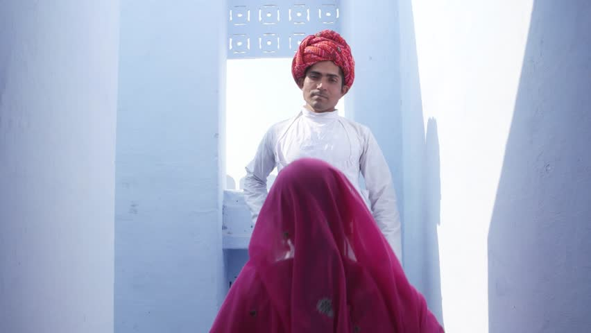 Woman in pink sari walks upto a man in red turban and white kurta and pose for camera in Rajasthan, India