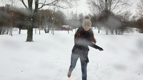 First person shot of snowball fight with young adult woman, she dodge from hit, then throw snow ball into camera. City park at december time, happy girl recreate together, play simple winter game
