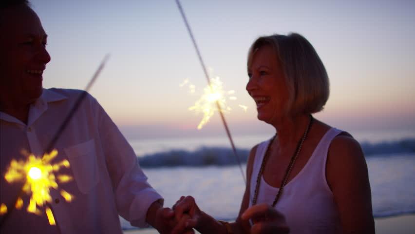 Senior mature Caucasian couple lifestyle travel resort healthcare dancing celebration sparklers beach sunset dusk    Shutterstock HD Video #22065076