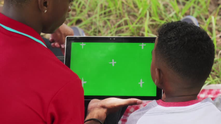 Happy black people in city park. African american family with young man and child using computer for internet and email. Leisure for man and boy with ipad tablet with green screen