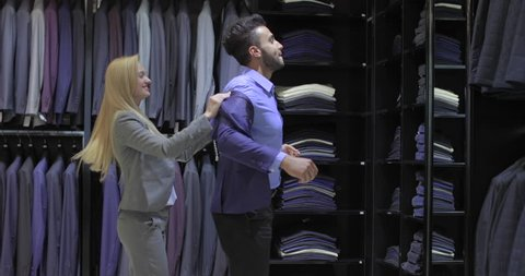 Business Man Trying Jacket Fashion Shop, Customer Choosing Clothes Retail Store, Shopping Consultant Woman Formal Wear Slow Motion 60 Fps