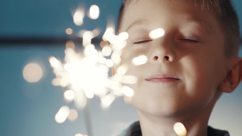 Happy adorable kid celebrating his birthday and make a wish indoor.