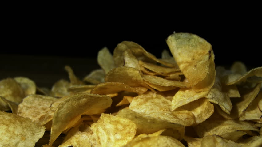 Potato Chips Rotating On Black Background. Potato chips are rotated on a black background. Close-up of yellow delicious chips randomly lying on a table. Excellent Footage for themes: Harmful food | Shutterstock HD Video #22145548