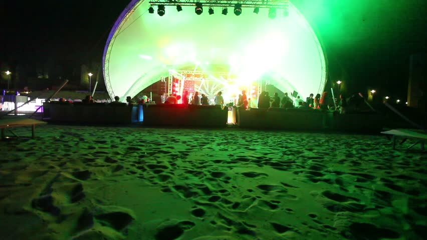 Stage and a disco on the beach. Night Beach Disco with illumination, concert. Celebration, holiday, feast. Dancing people with fun gladness on the discotheque entertainment. sandy beach,