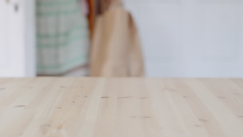 Young woman brings home a shopping bag with fresh fruits and vegetables. Closeup puts bag on the table
