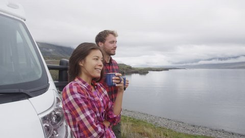 Travel couple by mobile motor home RV campervan. Travelers relaxing camping and enjoying traveling on Iceland in recreational vehicle. Man and woman enjoying coffee in Icelandic nature landscape.